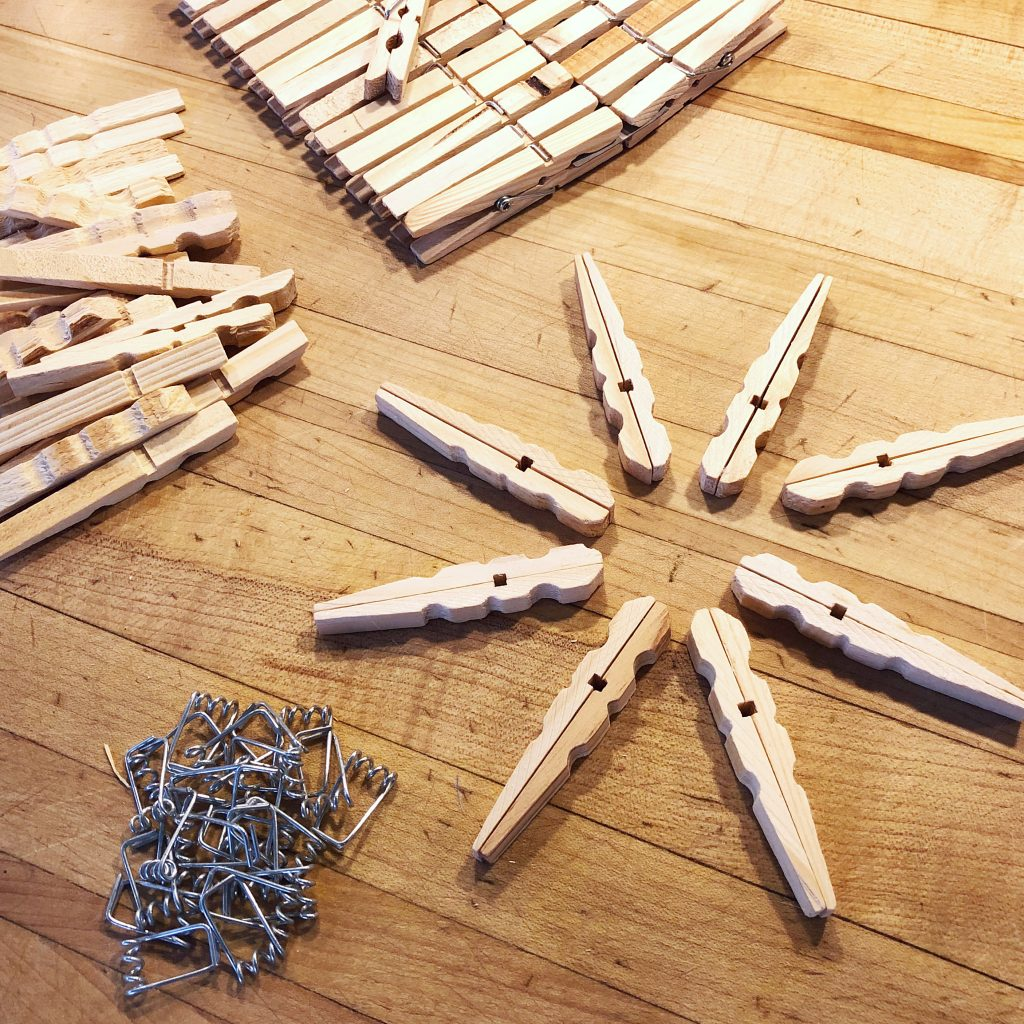 Taking apart wooden clothespins to make star ornaments.