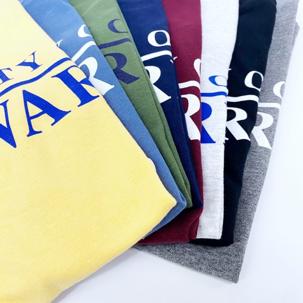 Detail photo of assorted darker colors of University of Delaware Skittles T-shirts