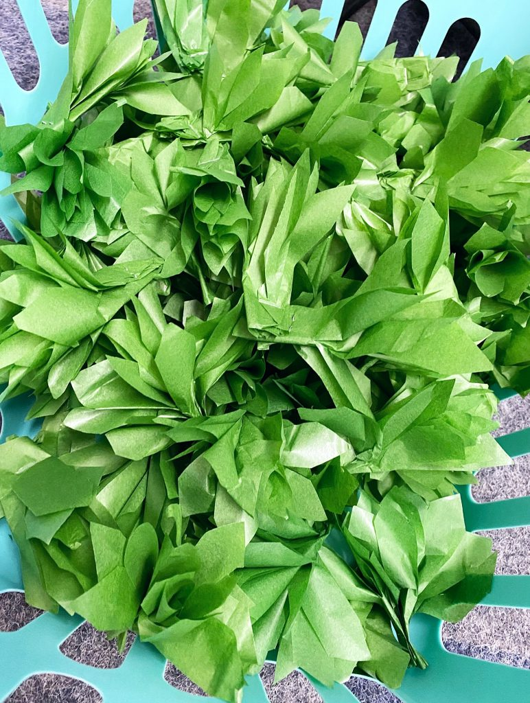 Big basket of completed green tissue paper leaves.