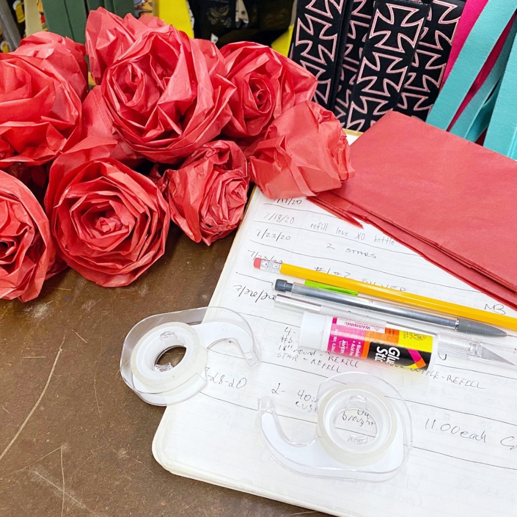 Red tissue paper roses and supplies to make them including red tissue paper, tape, glue stick and a pencil.