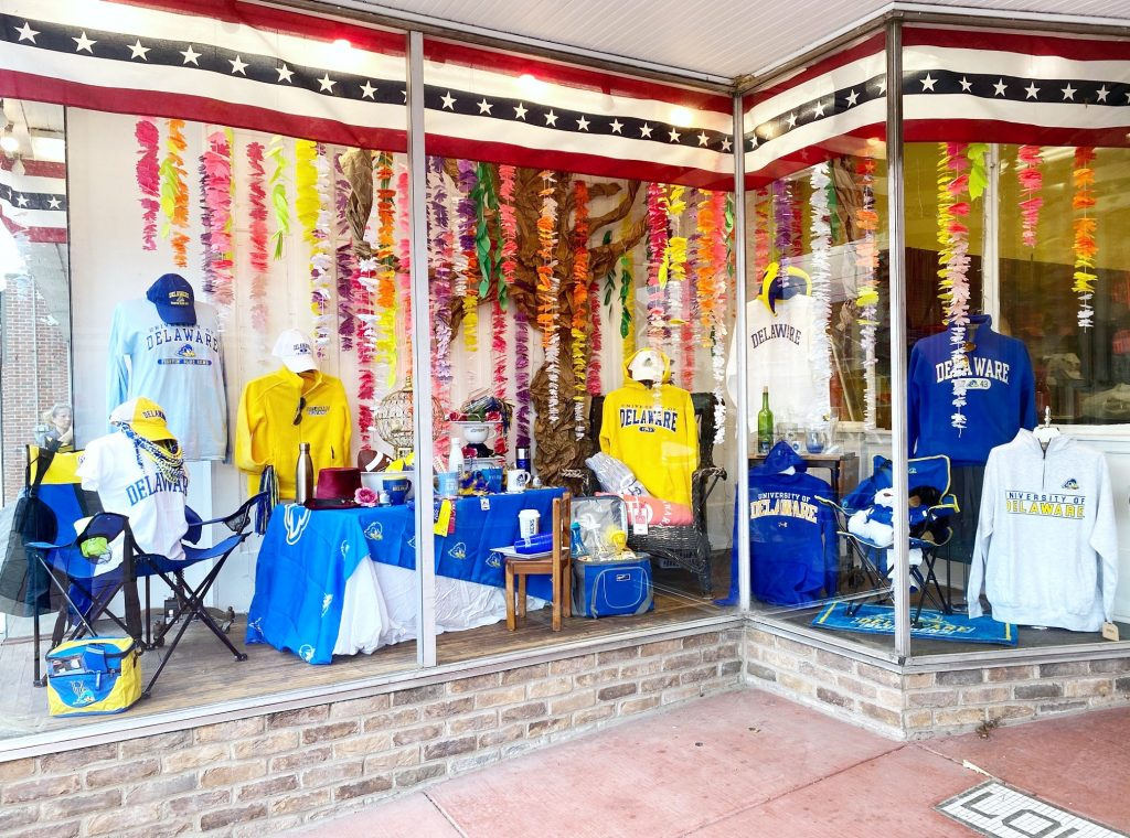 National 5 & 10 Mad Hatter's (Tailgate) Tea Party display window featuring blue and yellow University of Delaware apparel and tailgating/outdoor entertaining gear and accessories.