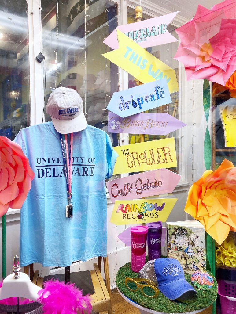 Store window details including colorful hand-painted directional sign, moss covered table and University of Delaware merchandise.